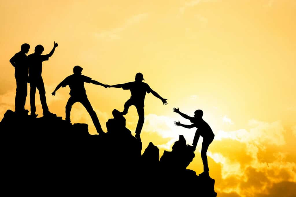Group of people on peak mountain climbing helping team work